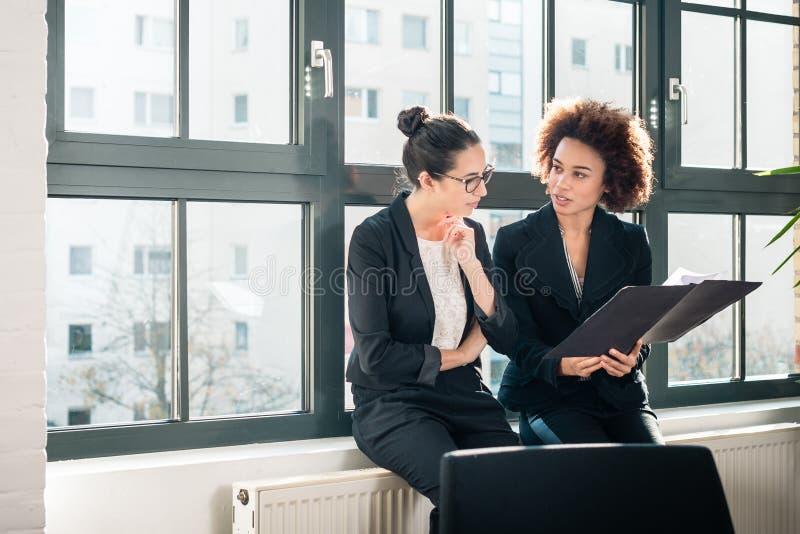 Två unga kollegor som granskar affärsrapporter under avbrott arkivbild