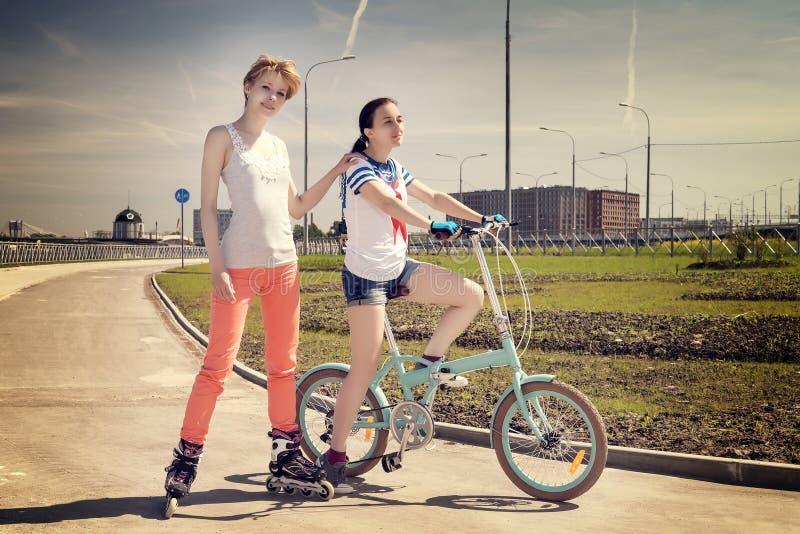 Två unga kvinnliga vänner en på en cykel, en på scates för en roler arkivbilder