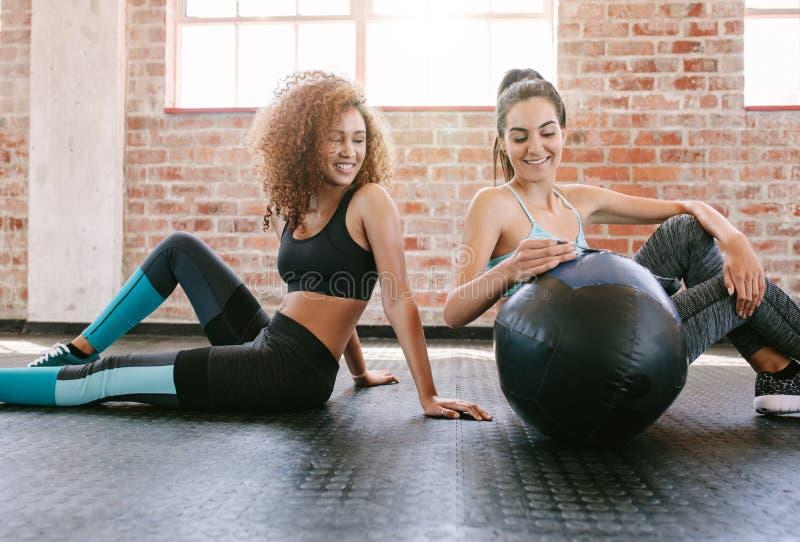 Två unga kvinnliga vänner i idrottshall med medicinbollen royaltyfri bild