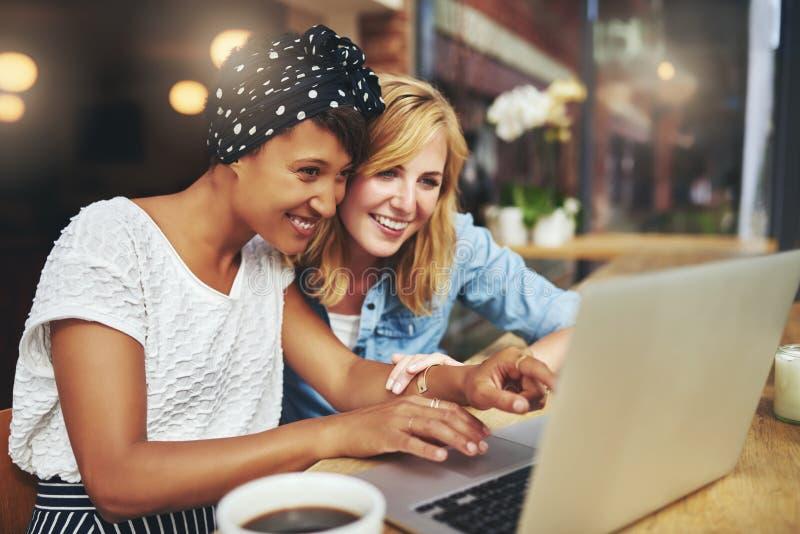 Två unga kvinnliga vänner som surfar internet royaltyfri fotografi