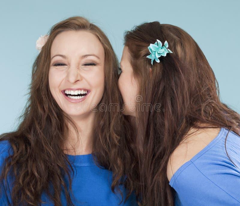 Två unga kvinnliga vänner som viskar skvaller royaltyfri fotografi