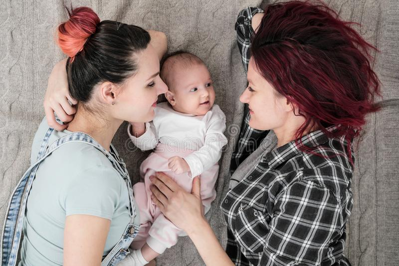 Två unga kvinnor, ett lesbiskt homosexuellt par, ligger på en filt med ett barn Homobröllop adoption royaltyfria bilder