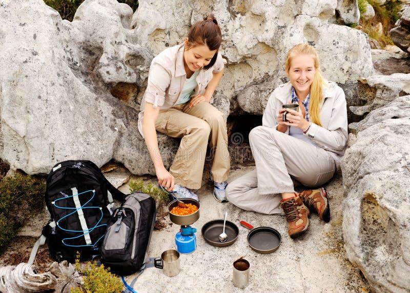 Två unga kvinnor förbereder något att äta royaltyfri fotografi