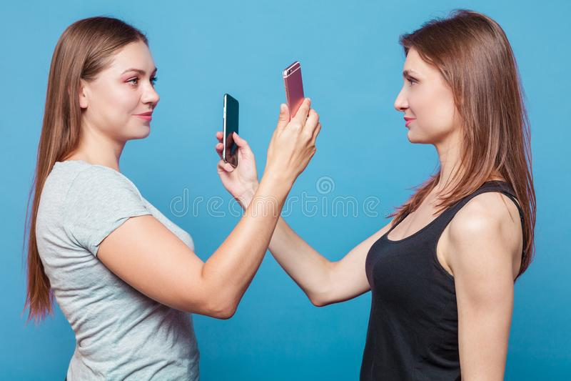 Två unga kvinnor gör fotoet av eath annan royaltyfria foton