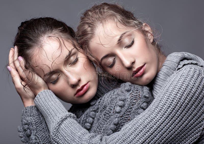 Två unga kvinnor i gråa tröjor på grå bakgrund härligt G arkivfoto