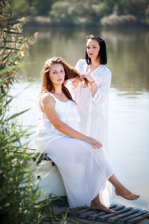 Två unga kvinnor i långa vita klänningar nära floden arkivbilder