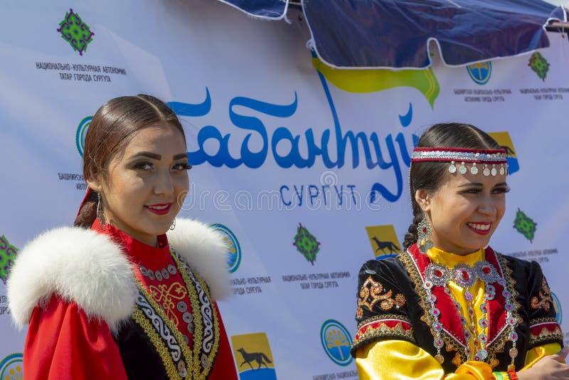 Två unga kvinnor i nationell Bashkir kläder och bak dem ettspråk 'Sabantuy Surgut ', arkivfoto