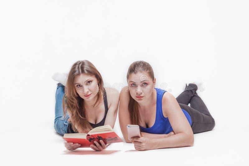 Två unga kvinnor lägger på golvet arkivbilder