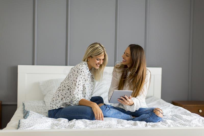 Två unga kvinnor med digitalt minnestavlasammanträde på säng royaltyfri foto