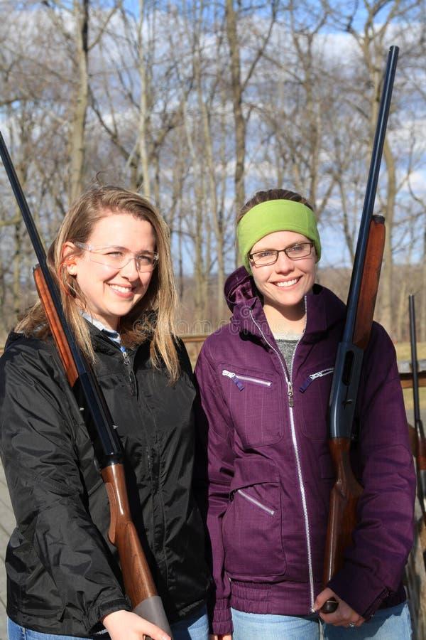 Två unga kvinnor med vapen på fällaskjutbana arkivfoton