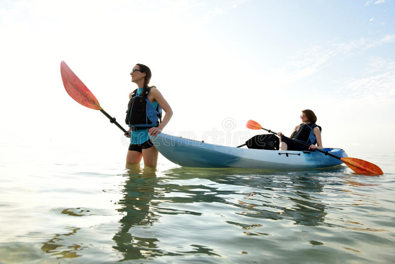 Två unga kvinnor och blå kajak i Atlantic Ocean royaltyfri fotografi