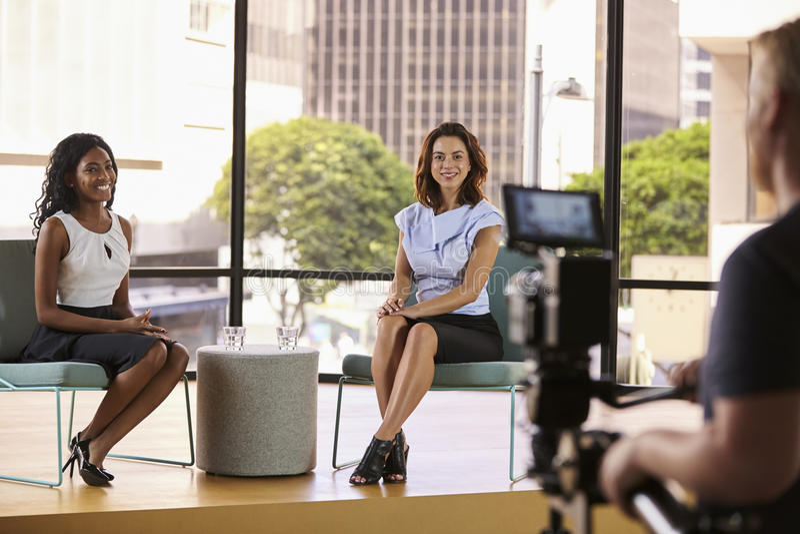 Två unga kvinnor på uppsättningen för filmandet av en TVintervju royaltyfria foton