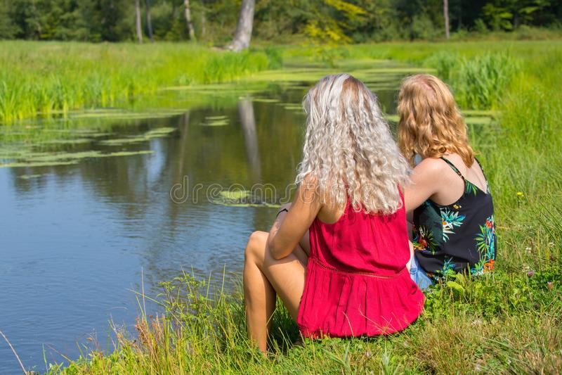 Två unga kvinnor sitter tillsammans på strand royaltyfri fotografi