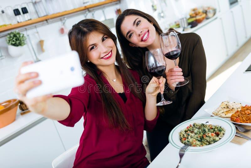 Två unga kvinnor som använder mobiltelefonen, medan äta i köket royaltyfri foto