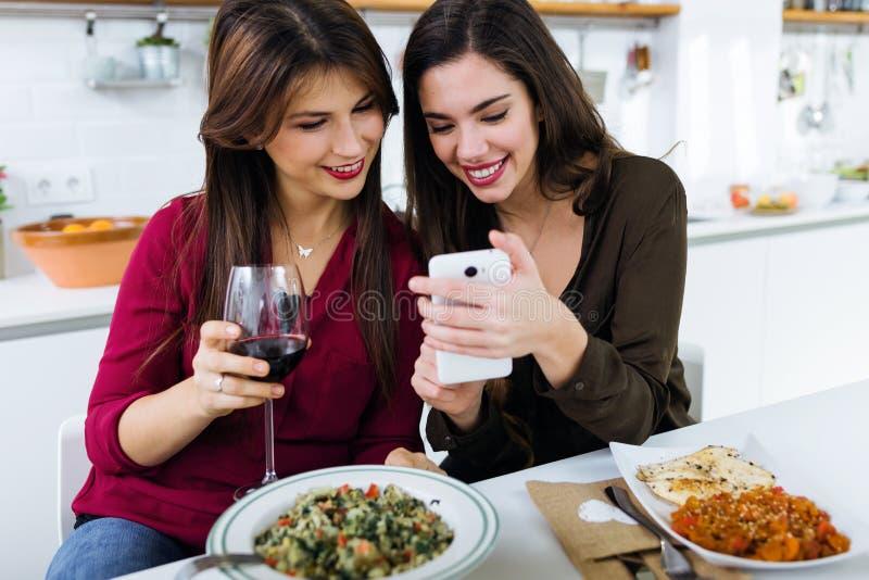 Två unga kvinnor som använder mobiltelefonen, medan äta i köket royaltyfria foton