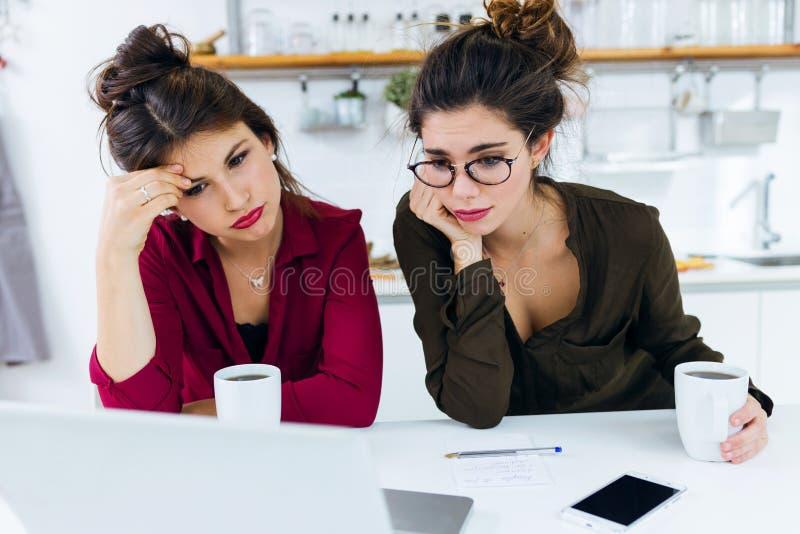 Två unga kvinnor som arbetar med bärbara datorn, medan dricka kaffe royaltyfria bilder