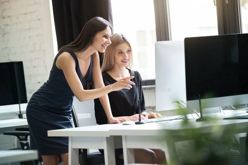 Två unga kvinnor som arbetar samman med datoren royaltyfri bild