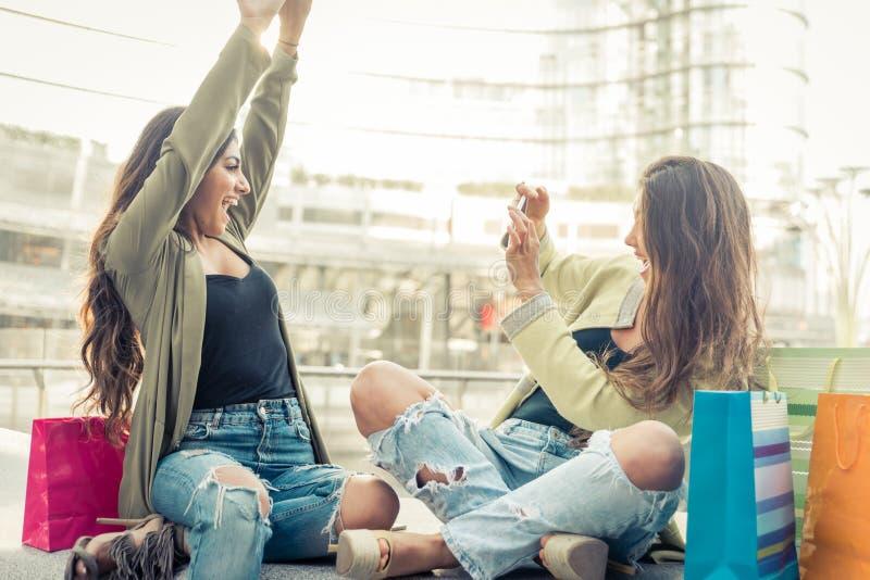Två unga kvinnor som har gyckel i centret arkivbilder