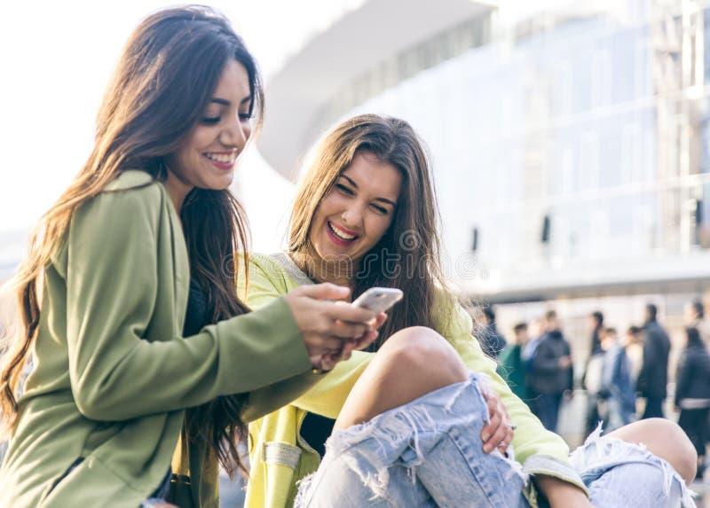 Två unga kvinnor som har gyckel i centret arkivfoton