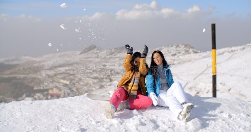 Två unga kvinnor som har gyckel i vintersnö arkivbilder