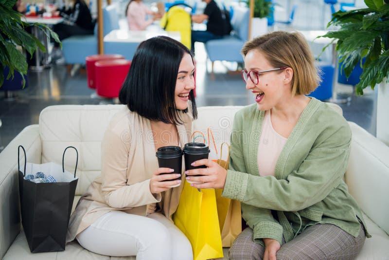 Två unga kvinnor som har kaffeavbrottet tillsammans på shoppinggallerian royaltyfria bilder