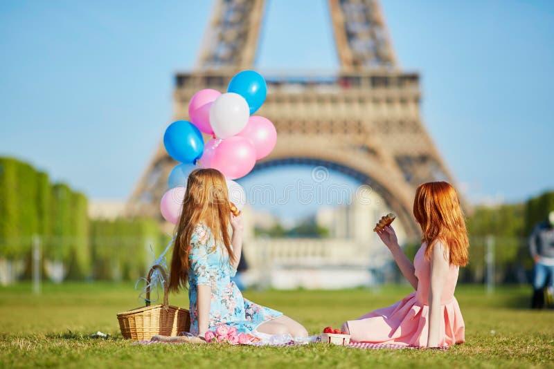 Två unga kvinnor som har picknicken nära Eiffeltorn i Paris, Frankrike royaltyfri foto