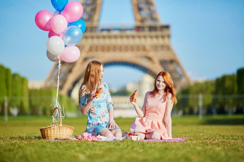 Två unga kvinnor som har picknicken nära Eiffeltorn i Paris, Frankrike arkivfoton