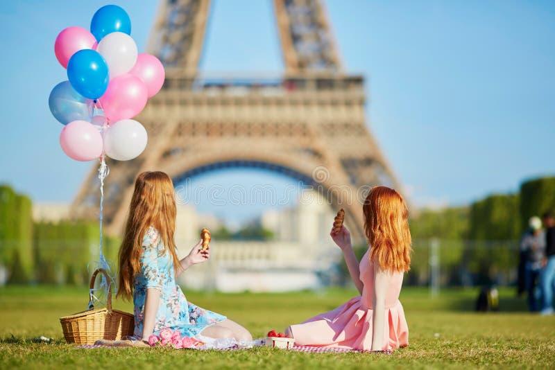 Två unga kvinnor som har picknicken nära Eiffeltorn i Paris, Frankrike royaltyfri fotografi