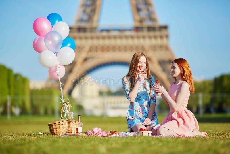Två unga kvinnor som har picknicken nära Eiffeltorn i Paris, Frankrike arkivfoto