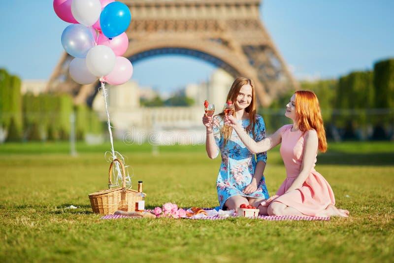 Två unga kvinnor som har picknicken nära Eiffeltorn i Paris, Frankrike fotografering för bildbyråer