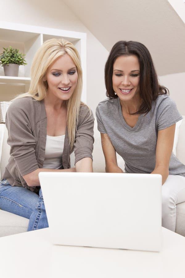 Två unga kvinnor som hemma använder bärbar datordatoren arkivbilder