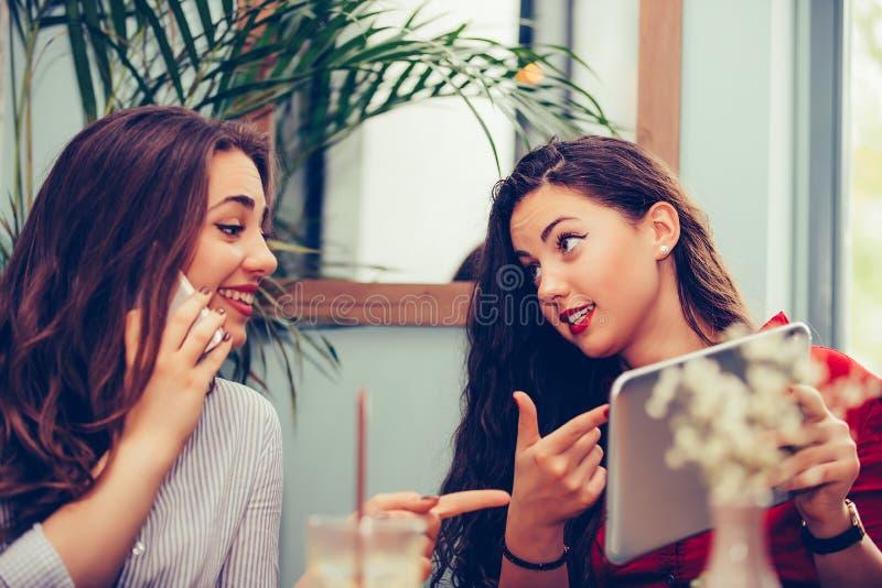 Två unga kvinnor som itting i kafé, dricker kaffe, talar och ser något på den digitala minnestavlan royaltyfri bild