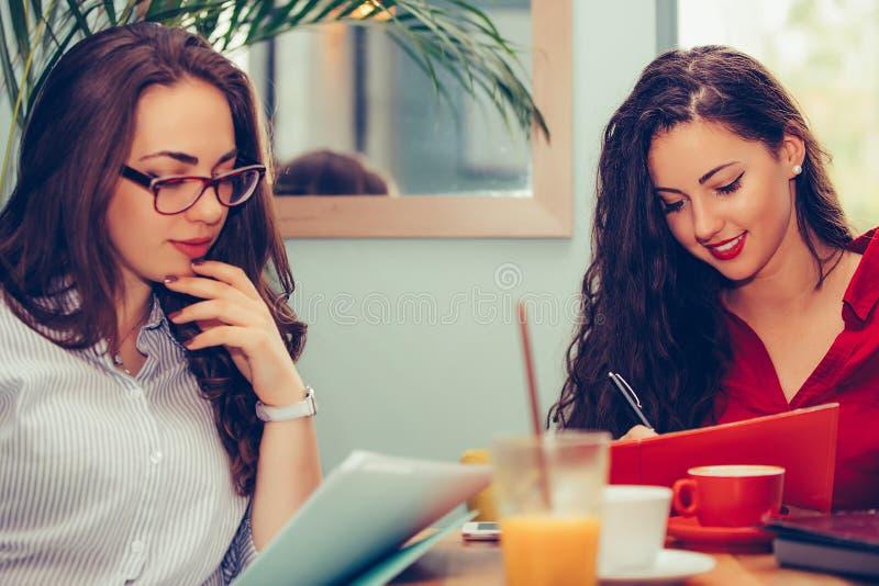 Två unga kvinnor som läser pappers- dokument som ser var att underteckna ett avtal arkivbilder