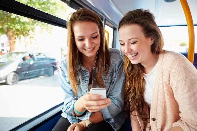 Två unga kvinnor som läser textmeddelandet på bussen fotografering för bildbyråer