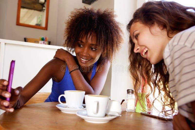 Två unga kvinnor som ler och ser mobiltelefonen royaltyfri fotografi