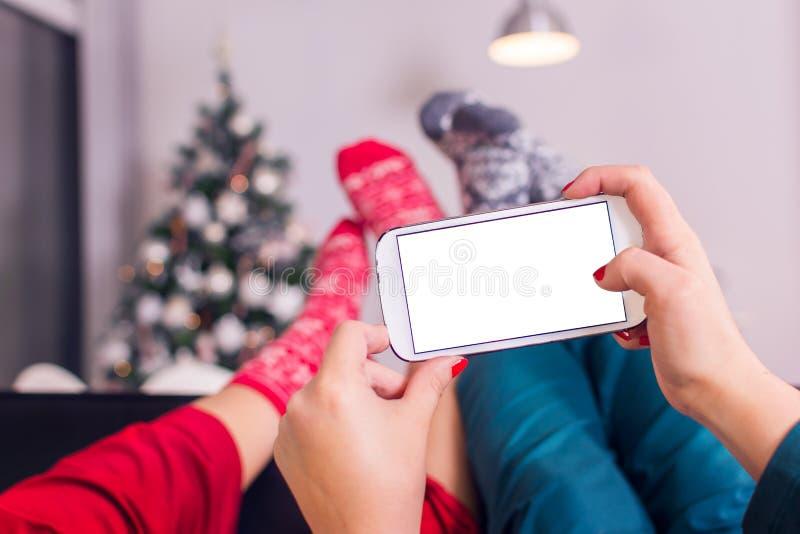 Två unga kvinnor som rymmer en smartphone fotografering för bildbyråer