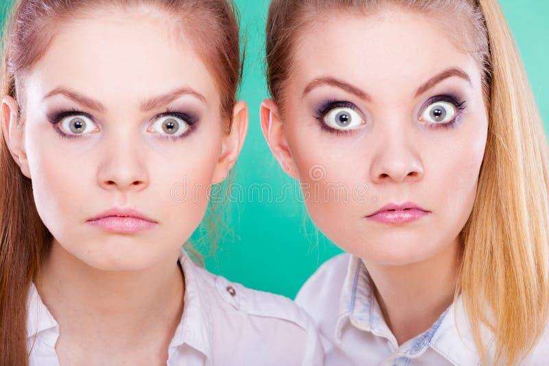 Två unga kvinnor som ser chockade royaltyfri foto