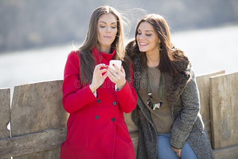 Två unga kvinnor som står bredvid staketet, ett av dem i ett rött arkivbilder