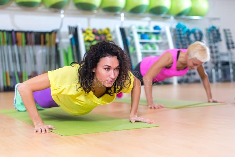 Två unga kvinnor som tillbaka gör satta övningar som är stående till med en schweizisk boll dem emellan Kvinnliga idrottsman nen  fotografering för bildbyråer