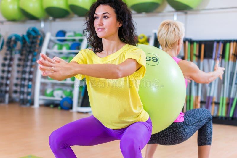 Två unga kvinnor som tillbaka gör satta övningar som är stående till med en schweizisk boll dem emellan Kvinnliga idrottsman nen  royaltyfria bilder