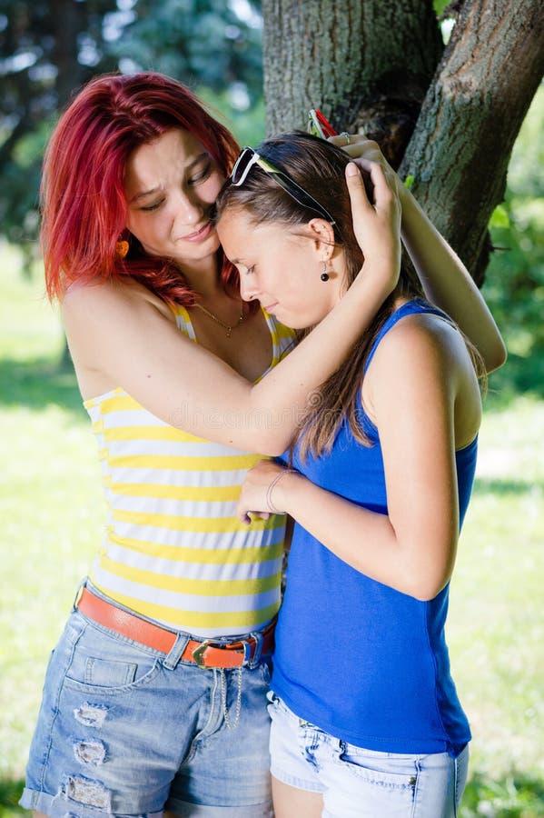 Två unga kvinnor som utomhus gråter arkivbild