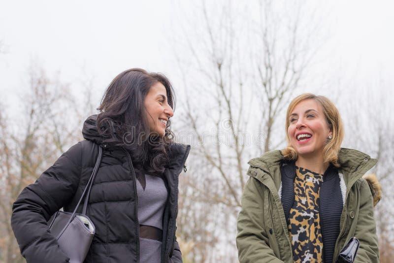 Två unga kvinnor som utomhus talar, ler och har roligt royaltyfri fotografi