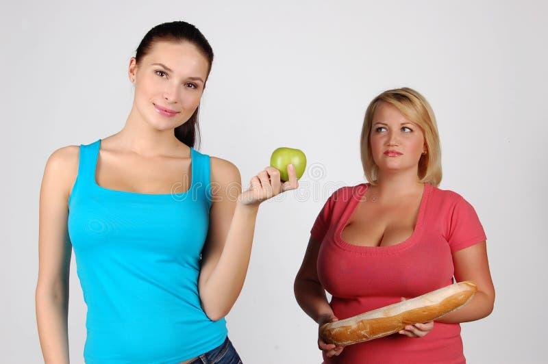 Två unga kvinnor som väljer mat för, bantar royaltyfria foton
