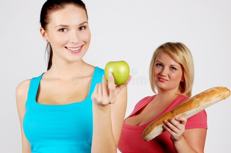 Två unga kvinnor som väljer mat för, bantar royaltyfri fotografi