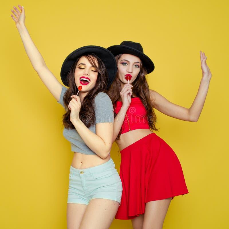 Två unga le nätta härliga flickor som bär hattar som rymmer ca arkivbild