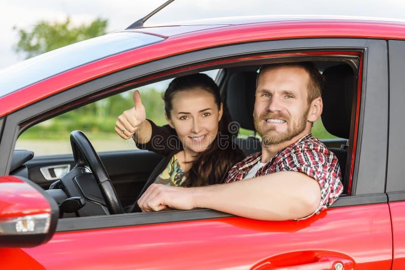 Två unga le personer i en röd bil royaltyfria foton
