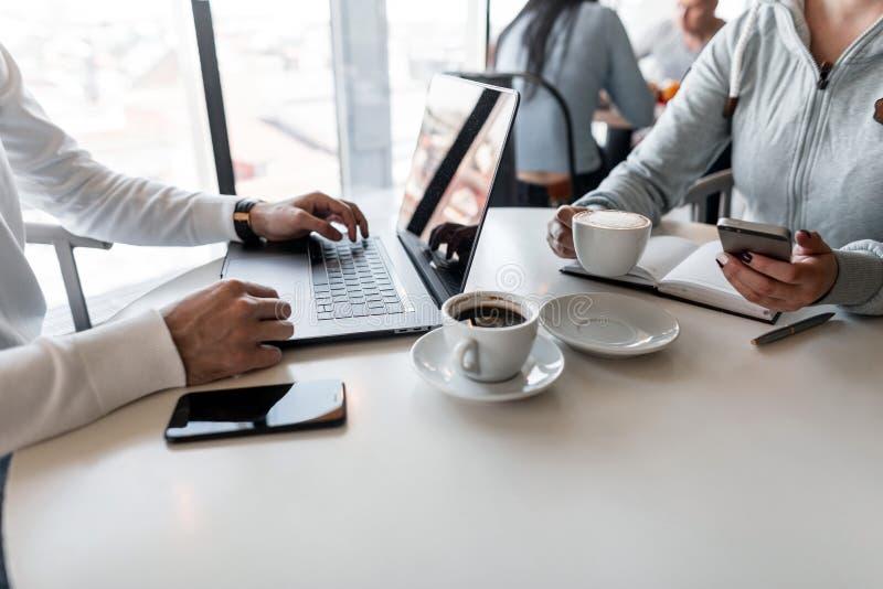 Två unga lyckade formgivare sitter med en bärbar dator med en notepad som diskuterar ett idérikt projekt och dricker kaffe arkivfoton