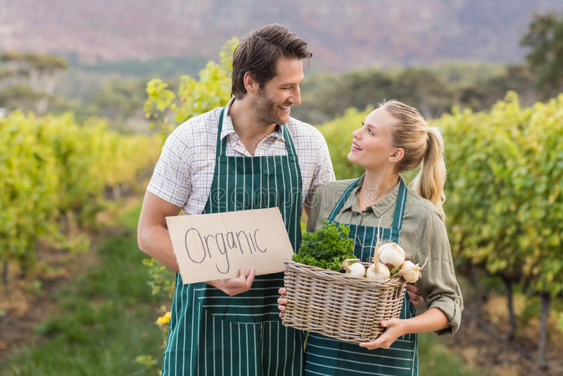 Två unga lyckliga bönder som rymmer ett tecken och en korg av grönsaker royaltyfria bilder
