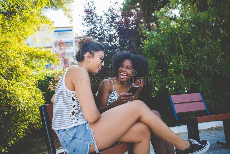 Två unga lyckliga flickor som sitter utanför att använda att skratta för mobil royaltyfri foto