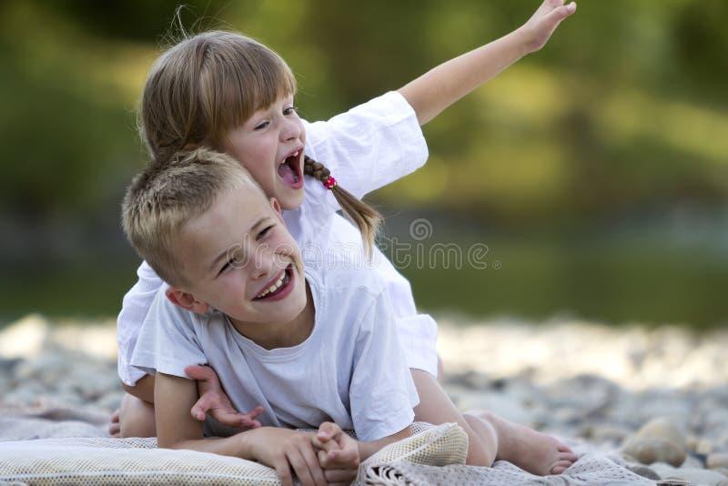 Två unga lyckliga gulliga blonda skratta barn, pojke och flicka, brot royaltyfri foto